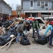 Stock Photo: QUEENS, NY - NOVEMBER 11: Volunteers cleaning debris and sand in Rockaway beach residential arefrom Hurricane Sandy in Queens, New York, U.S., on November 11, 2012.