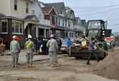 QUEENS, NY - NOVEMBER 11: U.S. Navy working on the streets ater massive destruction in the Rockaway Beach area due to impact from Hurricane Sandy in Queens, New York, U.S., on November 11, 2012. — Stock fotografie