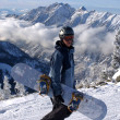 Snowboarder standing with mountain chain in the background — Foto de Stock
