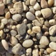 Naturally polished light rock pebbles background - Stock Photo