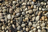 Naturally polished light rock pebbles background — Photo