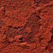 Chipped red paint on rusty textured metal background - Stock Photo