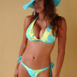 Exotic looking model posing in blue bikini and blue straw hat in front of wall — Stock Photo