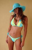 Egzotik görünümlü model mavi bikini ve mavi hasır şapka duvar önünde poz — Stok fotoğraf