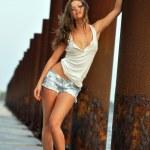 Beautiful sexy woman posing in jeans shorts at rusty boat marina — Stock Photo #18350247