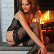 Beautiful tall redhead dressed in elegant lingerie sitting in front of working fireplace - Foto de Stock