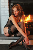 Beautiful tall redhead dressed in elegant lingerie sitting in front of working fireplace — Stock Photo