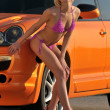 Young sexy girl posing by metallic orange sport car — Stock Photo #18399831