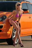 Young sexy girl posing by metallic orange sport car — Stock Photo