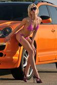 Chica sexy posando en coche deportivo naranja metalizado — Foto de Stock