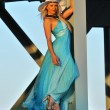 Fashion model in white hat and blue resort dress posing under the bridge at hot summer time — Stockfoto