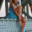 Fashion model in white hat and blue resort dress posing under the bridge at hot summer time — Stock fotografie