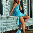 Fashion model in white hat and blue resort dress posing under the bridge at hot summer time — Stock Photo