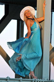 Fashion model in white hat and blue resort dress posing under the bridge at hot summer time — Stok fotoğraf