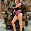 Model posing sexy in front of old rusty gear metallic background — Stock Photo #18441753