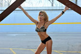 Tall blond woman posing very sexy in bikini in a parking lot garage exterior. — Stock Photo
