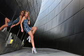Supermodel posing sexy in front of modern metallic wall background — Stock Photo