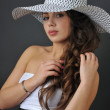 Beautiful young brunette girl posing pretty to camera in the studio wearing white dress and hat — Stock Photo #18627783