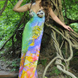 Beautiful brunette model posing pretty at tropical jungle wearing designers colorful dress — Stock Photo