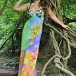 Beautiful brunette model posing pretty at tropical jungle wearing designers colorful dress — Stock Photo