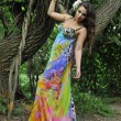 Beautiful brunette model posing pretty at tropical jungle wearing designers colorful dress — Stock Photo #18627935