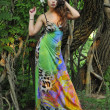 Beautiful brunette model posing pretty at tropical jungle wearing designers colorful dress - Stock Photo