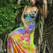 Stock Photo: Beautiful brunette model posing pretty at tropical jungle wearing designers colorful dress