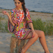 Beautiful brunette model posing pretty at tropical beach wearing short designers colorful dress — Stock Photo