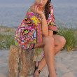 Stock Photo: Beautiful brunette model posing pretty at tropical beach wearing short designers colorful dress