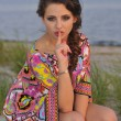 Beautiful brunette model posing pretty at tropical beach wearing short designers colorful dress — Stock Photo #18628005