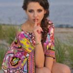 Beautiful brunette model posing pretty at tropical beach wearing short designers colorful dress — Stock Photo