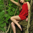 Beautiful young woman is leaning against a tree in the rain forest wearing sexy dress — Stock Photo