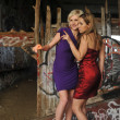 Two girls wearing colorful prom dresses on location — Stock Photo