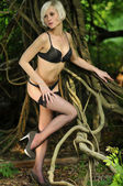 Beautiful young woman is leaning against a tree in the rain forest wearing Lingerie — Stock Photo