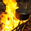 Cooking at night over campfire - Foto Stock