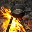 Cooking at night over campfire - Stock Photo