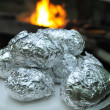 Making potatoes in foil over fireplace in campground - Stock Photo
