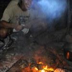 Приготовление ночью в палаточном лагере у костра — Стоковое фото