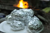 Making potatoes in foil over fireplace in campground — Stock Photo