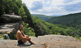 A male tourist stands on a boulder ridge overlooking a portion of panorama. View from ledge on top of Kaaterskills waterfall in the Catskills Mountains of New York — Stock Photo
