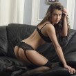 A young brunette woman posing sexy in lingerie at black leather sofa love seat — Stock Photo