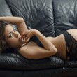 Portrait of young brunette woman posing sexy in lingerie at black leather sofa love seat — Stock Photo