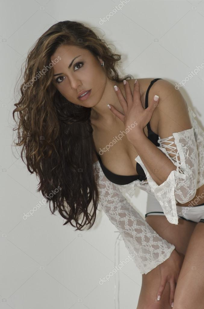 Sexy woman with long brunette hair and wearing lacy white lingerie, three quarter standing sideways on white   Stock Photo #19153153