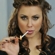 Portrait of pretty young smoking woman during makeup and hairstyling process - Stock Photo