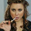 Stock Photo: Portrait of pretty young smoking womduring makeup and hairstyling process