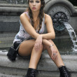 Fashion model sitting in front of fountain in New York City park — Stock Photo