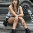 Fashion model sitting in front of fountain in New York City park - Stock Photo