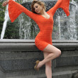 Fashion model posing in short red dress in front of fountain in New York City park - Stok fotoraf