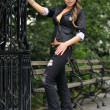 Fashion model posing in black jacket and police hat in front of metal gate in New York City park — Stock Photo