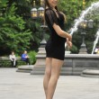 Stock Photo: Fashion model posing in short black dress and NYPD police hat in front of fountain in New York City park